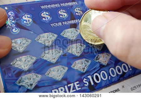 Coquitlam BC Canada - June 04, 2015 : Woman scratching lottery ticket The British Columbia Lottery Corporation has provided government sanctioned lottery games in British Columbia since 1985.