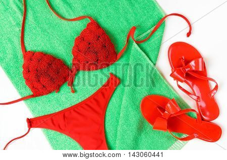 Red Bathing Suit And Red Flip-flops On Green Towel. Summer Clothes