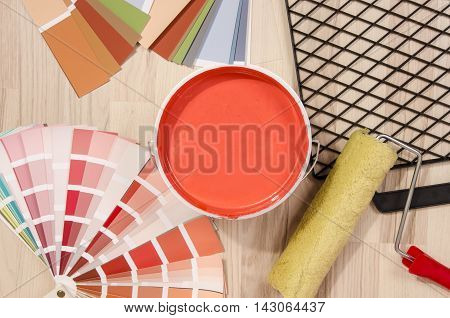 Coral red paint can. Samples with different shades of red and can of red paint with paint roller and accessories. Swatches and paint on the floor.