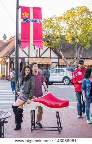 Solvang, USA - February 13, 2016: A tourist couple posing for photo on Danish style shoe clog with city sign and flag