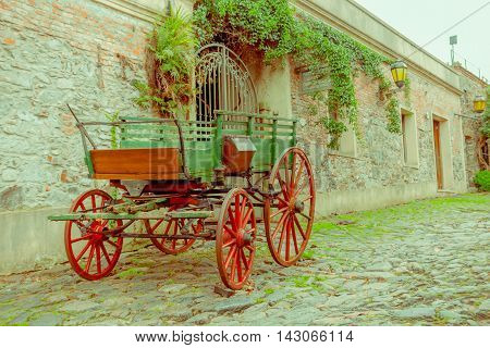 COLONIA DEL SACRAMENTO, URUGUAY - MAY 04, 2016: nice entrance of an ancient house with an old cart parked in the street.