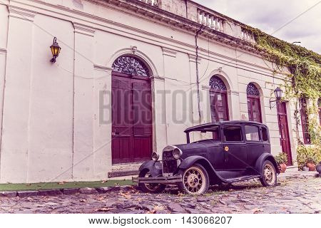 COLONIA DEL SACRAMENTO, URUGUAY - MAY 04, 2016: colonial style house with some wood doors and windows, ancient car parked outside the house.