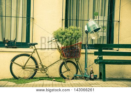 COLONIA DEL SACRAMENTO, URUGUAY - MAY 04, 2016: nice obsolete bycicle parked outside a house next to a bench.