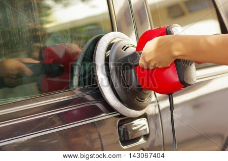hands holding a power buffer machine cleaning a car.