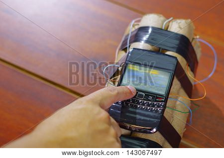 human setting the timer on a cellphone connected to explosives. poster
