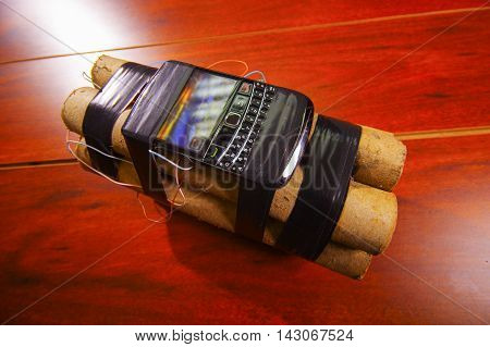 set of explosives conected to a cellphone laying on the ground.