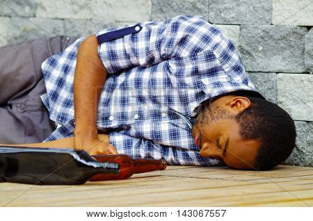 Man wearing casual clothes lying drunk passed out on wooden surface next to grey brick wall, empty bottle beside him.