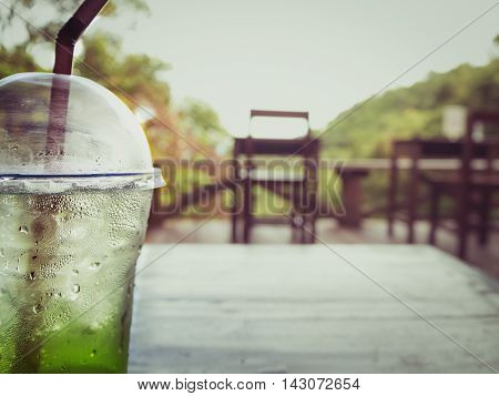 Close-up of a glass of ice kiwi soda with drop of water on wooden table with blurred view of coffee shop surrounded by nature at Chiangmai Thailand. Vintage filter and warm tone