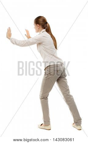 back view of woman pushes wall.  Isolated over white background. Rear view people collection. backside view of person. Skinny girl in white denim suit shoves the load side.