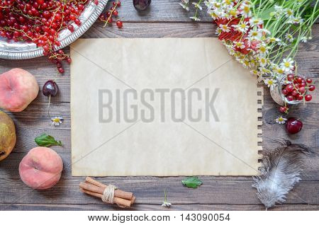 Vintage paper mock up on rustic wood background with natural style decorations. Berries and fruits border. Blank template, art letters, background space for text, vintage mock up.