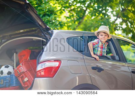 Adorable little kid boy sitting in car just before leaving for summer vacation with his parents. Happy child with suitcases and toys going on journey.