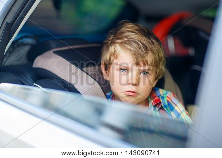 Sad little kid boy sitting in car in traffic jam during going for summer vacation with his parents. Tired, exhausted child not happy about journey.