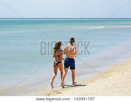 Odessa, Ukraine - July 27, 2016: Couple of young people running or jogging on the beach Young tanned happy man and woman enjoying vacation in the summer and sea, and stroll on the beach