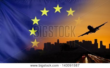 Travel and transport concept with skyline silhouette highway traffic and airplane at sunset merged with real fabric flag of Europe