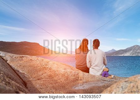 Romantic Couple sitting on the big stone watching the sunset together