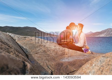 Romantic Couple sitting on the big stone kiss together with sunset