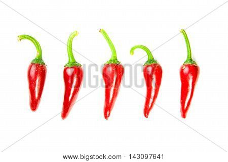 Five ripe red Chilli peppers on over white