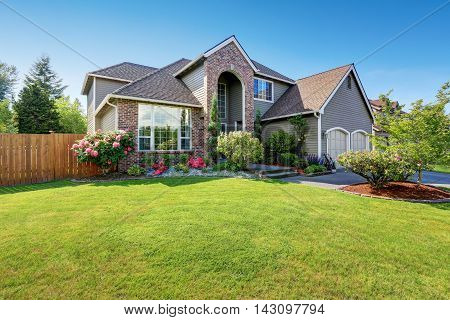Luxury house exterior with brick and siding trim and double garage. Well kept garden around. Northwest USA poster