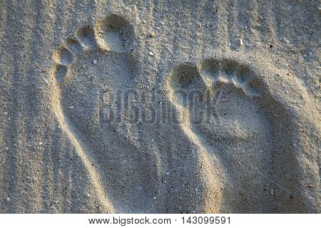 Prints of male feet on sand ,