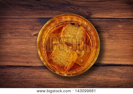 Top Of View Of Whiskey In Glass With Ice Cubes On Wood Table Background