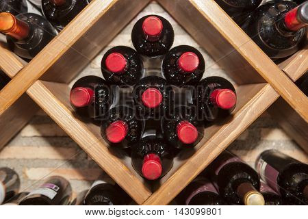 Rhomboid wine rack with multiple bottles of spanish red wine lying in storage