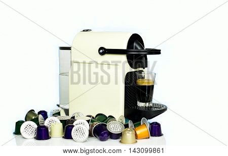Selected focus glasses of Espresso shot on Espresso machine with group of capsules in white background