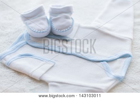 baby clothes, babyhood, motherhood and object concept - close up of white cardigan and bootees for newborn boy on towel