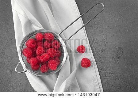 Fresh raspberry in sieve on grey table