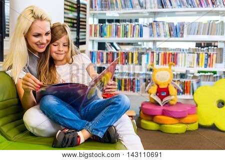 Mother With Little Girl Read Book Together