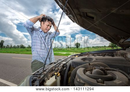 young stressed man having trouble with his broken car looking in frustration on failed engine