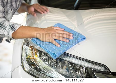 A man cleaning car with microfiber cloth car detailing (or valeting) concept
