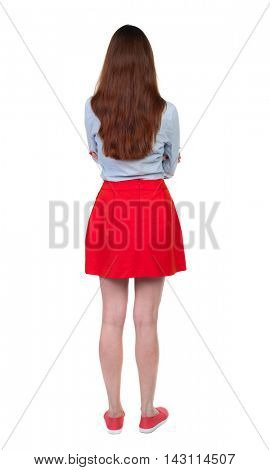 back view of standing young beautiful  woman.  girl  watching. Rear view people collection.  backside view of person.Long-haired brunette in red skirt standing with his arms crossed.
