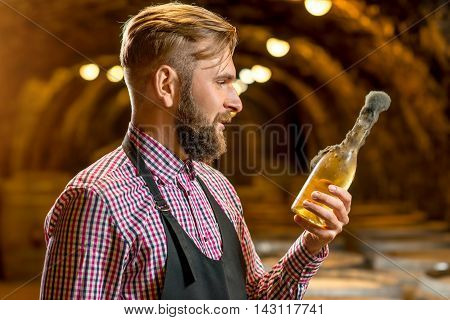 Sommelier holding old bottle of white wine with famous black mold in a wine cellar in Hungary