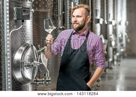 Portrait of a handsome wine maker in working apron with the wine glass at the manufacture with metal tanks for wine fermentation. Wine production at the modern factory poster