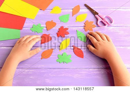 Child cut out of colored paper fall leaves. Kid doing fall paper crafts. Children hands, scissors on lilac wooden background. Simple crafts for toddlers, preschool and kindergarten
