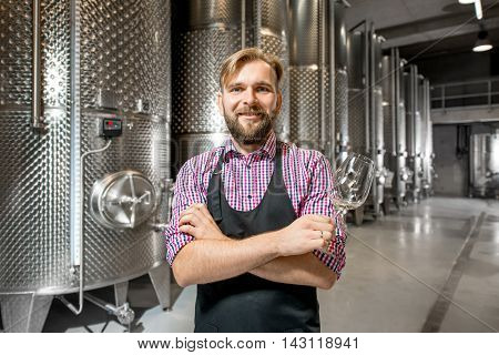 Portrait of a handsome wine maker in working apron with the wine glass at the manufacture with metal tanks for wine fermentation. Wine production at the modern factory