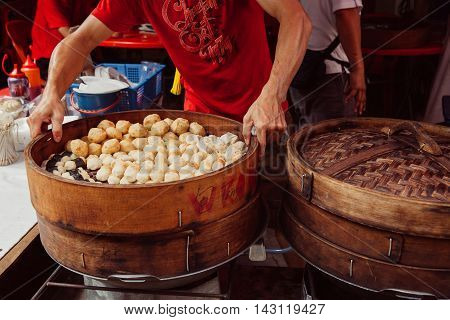 KUALA LUMPUR MALAYSIA - MARCH 17: Young man cooking chinese traditional steamed buns at the street food stall in Chinatown Kuala Lumpur Malaysia on March 17 2016.