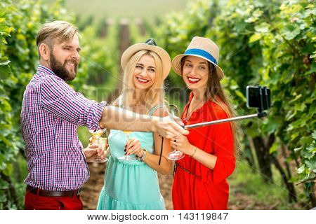Three friends with hats and wine glasses having fun making selfie photo with smartphone and selfie stick on the vineyard