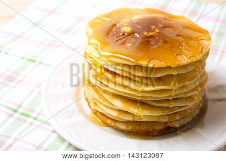 Stack of breakfast pancakes with honey on the white plate. Homemade pancakes served for breakfast.