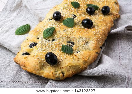 Italian bread focaccia with olive garlic and herbs on the linen napkin. Homemade traditional Italian bread focaccia.