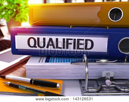 Blue Ring Binder with Inscription Qualified on Background of Working Table with Office Supplies and Laptop. Qualified Business Concept on Blurred Background. 3D Render.