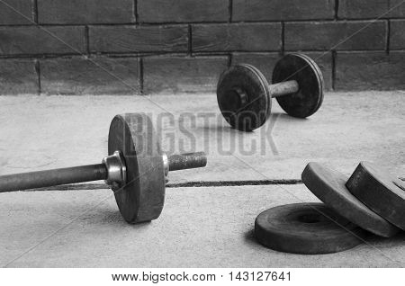 Weight barbell bar with dumbbell brick wall background