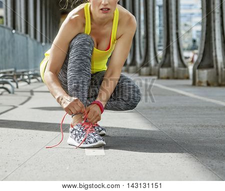 Outdoors fitness in Paris. young woman jogger tying shoelaces on Pont de Bir-Hakeim bridge in Paris poster