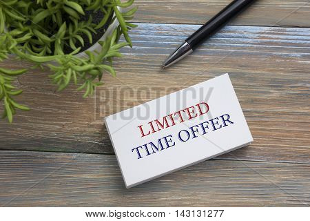 Text Limited time offer on white paper book and office supplies on wooddesk. Business concept