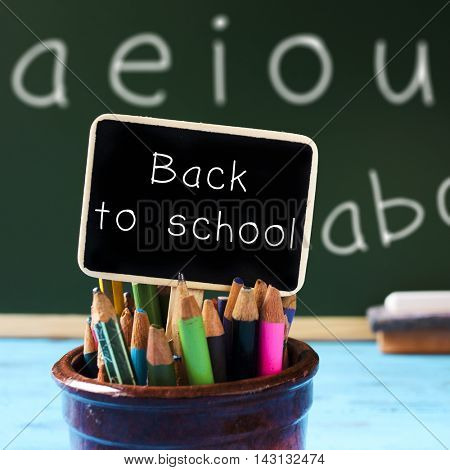 closeup of a black signboard with the text back to school placed in a pot full of pencil crayons of different colors, and a chalkboard with the vowels handwritten in it in the background