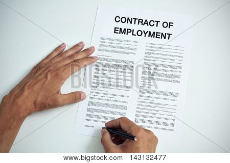 closeup of a young caucasian man about to sign a contract of employment