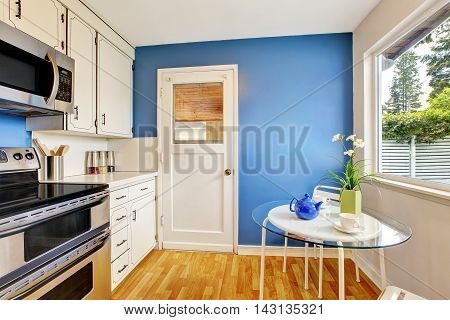 Kitchen Room With White Cabinets, Blue Walls And Glass Able