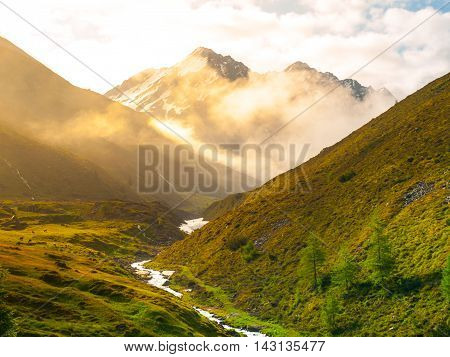 Morning in the alpine valley with haze illuminated by rising sun, green meadows and small river, Austria.
