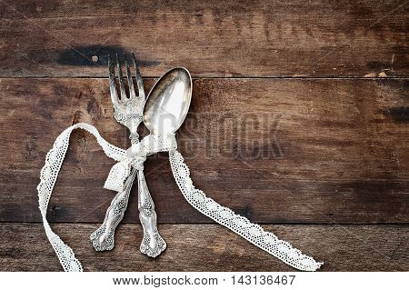 Antique silverware spoon and fork tied with lace ribbon over a rustic old wooden background with a grunge like feel. Image shot from overhead.
