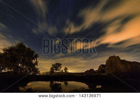 Panska Skala and stars in night motion clouds geological formation stone organ Kamenicky Senov Czech Republic